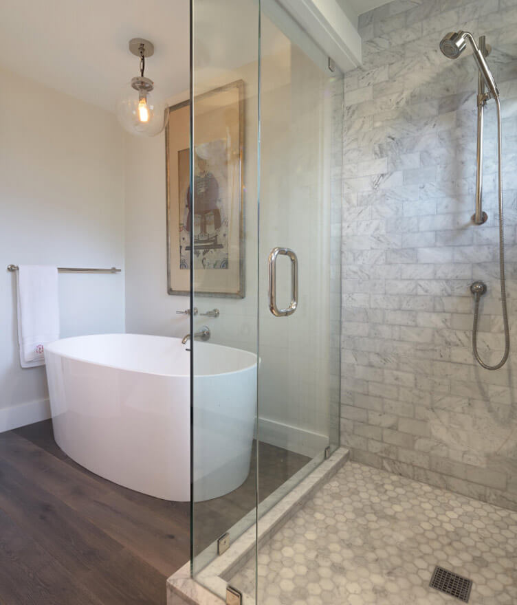A bathroom with wood floors and light gray tile.