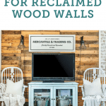A reclaimed wood wall behind two chairs and a tv