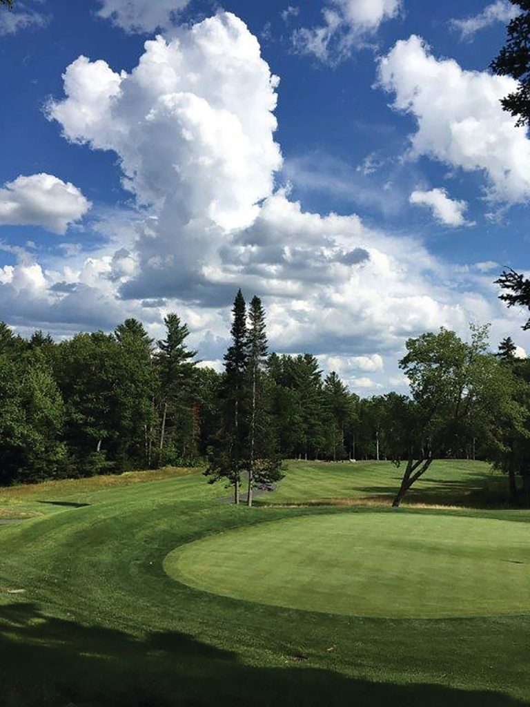 18-hole golf course of the Eastman community in New Hampshire on a semi-cloudy day with a surrounding forest.