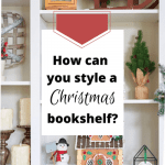 Open shelves in a Christmas bookcase decorated with Christmas decor, including a gingerbread house with an elf-on-the-shelf on the roof.