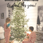 Two children beside the glowing Christmas tree in red and white striped pajamas.