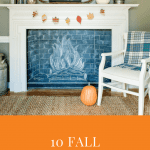A fireplace frames a chalkboard drawn with chalk to look like a buring fire. On the mantel is a wreath of fall leaves and a white pumpkin.