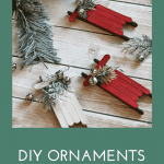 Three DIY ornaments made with painted popsicle sticks, spruce tips and mini silver bells made to look like sleighs.
