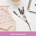 A baby pink scarf being knit with a knittign needle and a cup of coffee beside a sprig of lavender