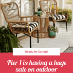 A pair of sand-colored rattan chairs have blacka nd white stripe throw pillows in them on a farmhouse style porch